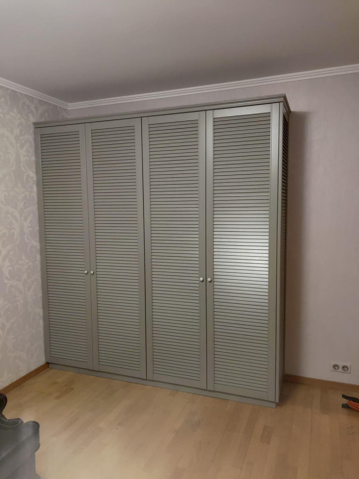 Серого цвета шкаф с жалюзийными фасадами из массива